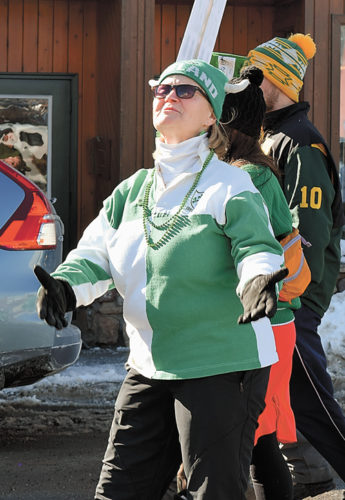"""Kelly Morgan makes a """"Kiss me, I'm Irish"""" gesture as she marches with the O'Reilly-Morgan clan in Saranac Lake's St. Patrick's Day parade. (Enterprise photo — Chris Knight)"""