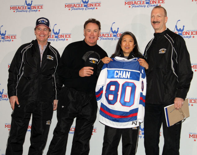 Carol Chan of Washington, D.C., poses after being named to the Gold Team Monday during the Miracle on Ice Fantasy Camp draft at the Lake Placid Conference Center. From left are Rob McClanahan, Jim Craig, Chan and team coach Ken Morrow. In all, 14 of the 19 members of the 1980 U.S. Olympic hockey team and 56 campers are participating in the event, which began on Sunday and wraps up on Thursday. (Enterprise photo — Andy Flynn)