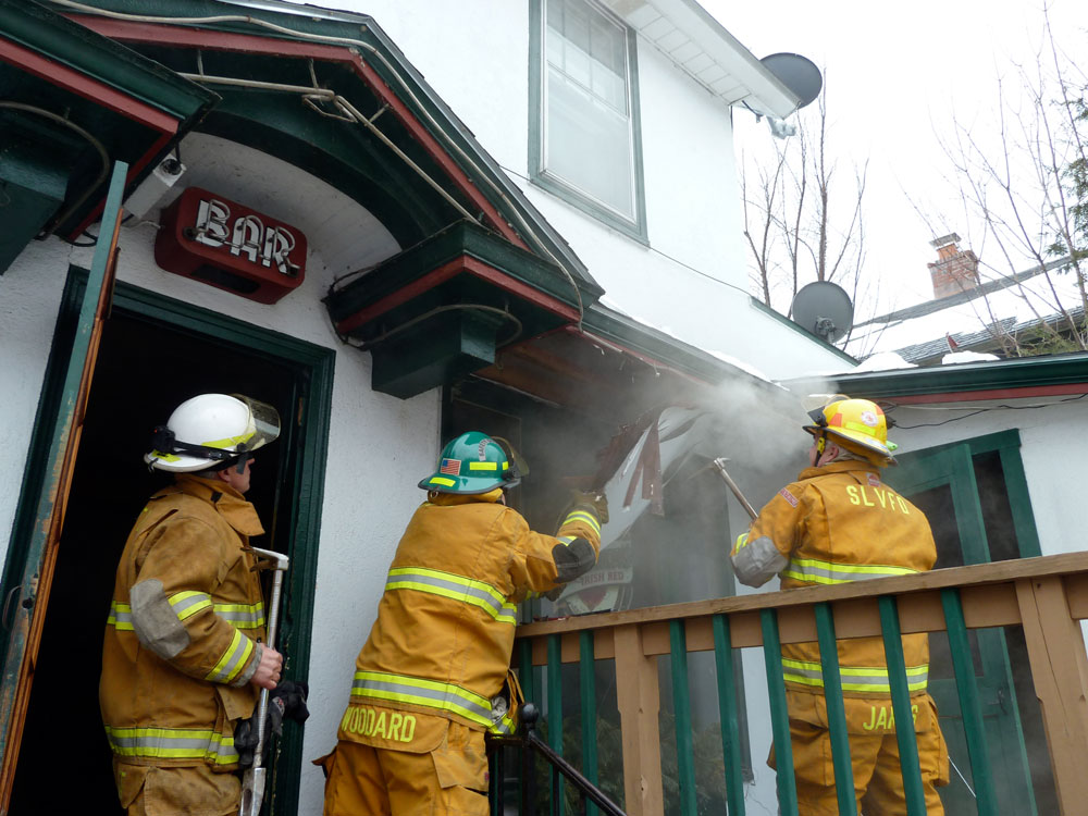 Smoke pours out as Saranac Lake firefighter Vernon James uses a crowbar to rip open the eaves of the Belvedere Restaurant early Tuesday afternoon to extinguish a fire smoldering in the front wall of the bar. (Enterprise photo — Peter Crowley)