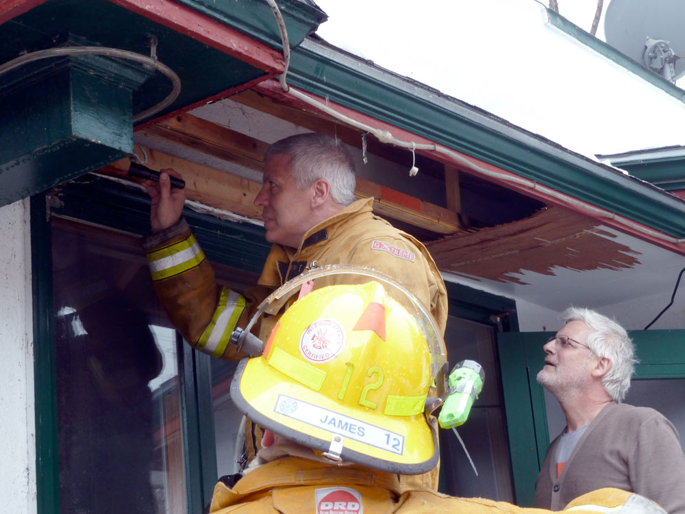 Belvedere Restaurant co-owner Jerry Cavallo, right, watches as Saranac Lake fire Chief Brendan Keough peers at wiring inside the Belvedere's ripped-open bar entrance after extinguishing a fire inside that wall early Tuesday afternoon.  (Enterprise photo — Peter Crowley)