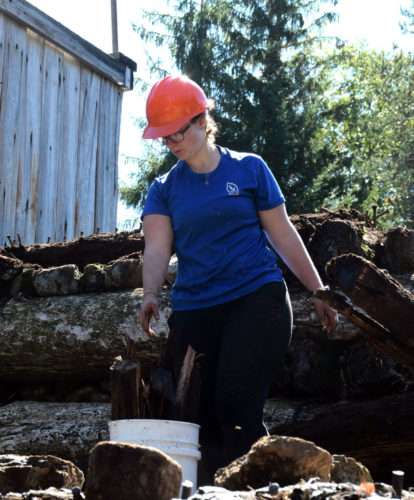 Student Conservation Association intern Victoria Challingsworth collects loose pieces of wood from the top of Marcy Dam in September 2015 as an SCA-AmeriCorps crew dismantles the damaged dam's top tier for the state of New York. (Enterprise photo — Shaun Kittle)