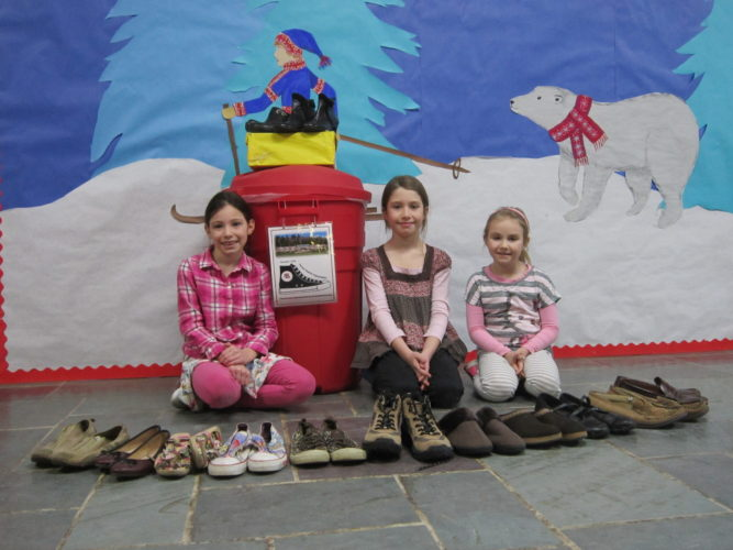"""Bloomingdale Elementary School second-grade students Ashlyn Tomaszewski, Ilianna Bruno and Eliza Endries display a few of the shoes collected for the Saranac Lake High School's """"Share Your Soles"""" shoe drive.  (Photo provided — Diane Chase)"""