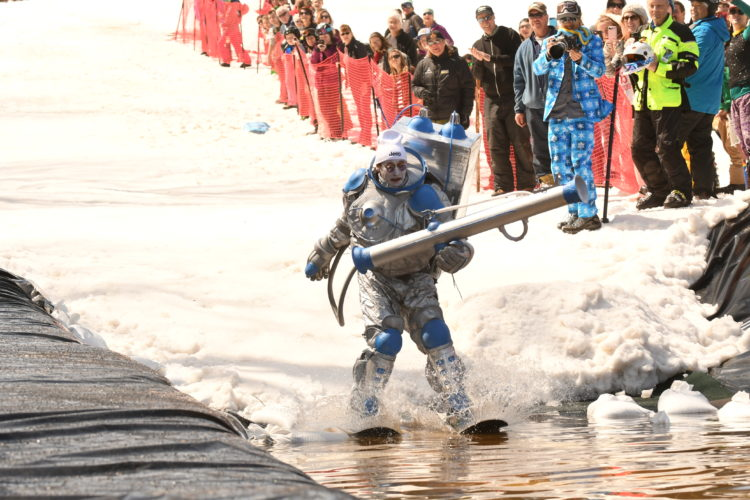 "Dressed as Mr. Freeze from ""Batman"" with a snowboard cut in half strapped to his feet, Saranac Lake's Tim Smith hits the water in Sunday's International Pond Skimming contest at Whiteface Mountain. (Enterprise photo — Lou Reuter)"