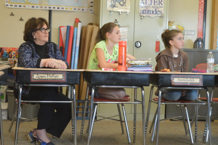 New York state Education Commissioner MaryEllen Elia listens to L.P. Quinn Elementary School social studies teacher Tracy Klossner's lesson alongside sixth grade students Lucy Edwards and Sierra Welch during Elia's visit to the school Tuesday. (Enterprise photo — Antonio Olivero)