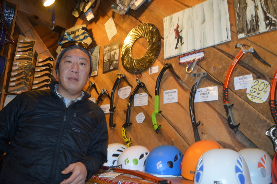 Matt Horner of Keene, an ice climber who was injured in a fall at Chapel Pond two months ago, stands beside a photo of himself climbing and one of his pieces of art at The Mountaineer in Keene Valley, made out of Charlet Moser ice axe picks. Horner also just designed a new interior sign for the store made out of 44 picks and will build a larger-than-life ice axe for the store's exterior.(Enterprise photo — Antonio Olivero)