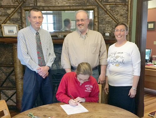 Saranac Lake High School senior Brittany Shumway signs a national letter of intent to run cross country and track at Roberts Wesleyan College in Rochester while her coach Joe Garso, left, and parents Rodney and Lisa Shumway look on. Shumway, a four-letter high school athlete who won the Section VII, Class C individual title and was named to the second team all-state this year, plans to study forensics in college. Roberts Wesleyan is a Division II school with a strong cross country running program that has captured three East Coast Conference titles in a row and sent several runners to the NCAA Division II championships. (Photo provided)