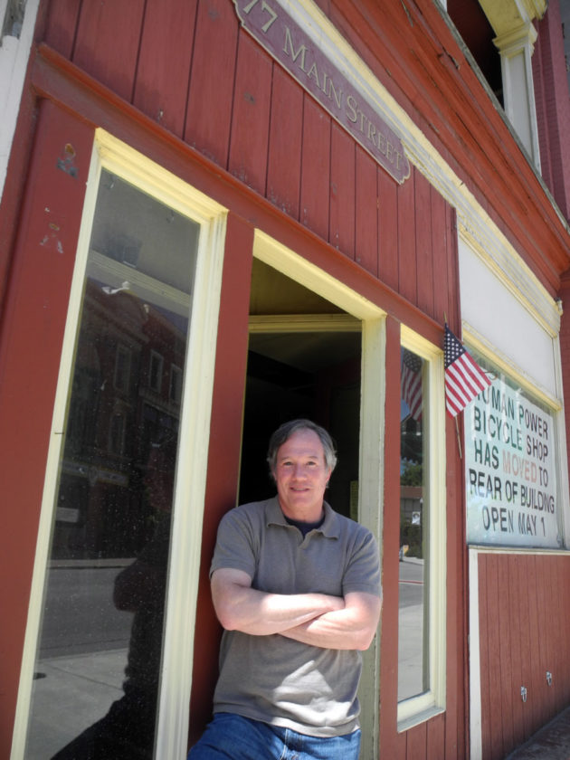 Real estate developer Wayne Zukin poses at 77 Main St., one of several commercial buildings he owns in downtown Saranac Lake, in June 2015. (Enterprise photo — Chris Knight)