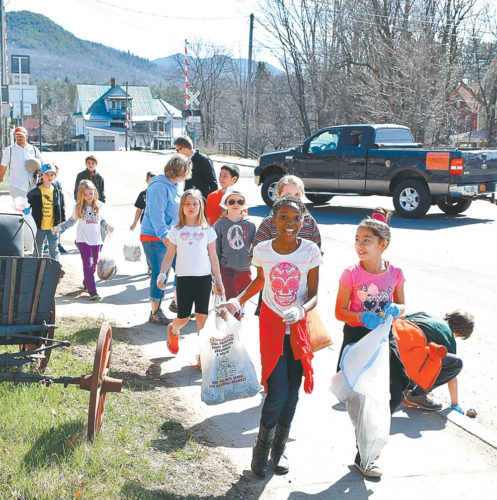 Petrova Elementary School students pick up litter along train tracks at Bloomingdale Avenue and Margaret Street, Saranac Lake, for Earth Day last April. (Enterprise photo — Justin A. Levine)