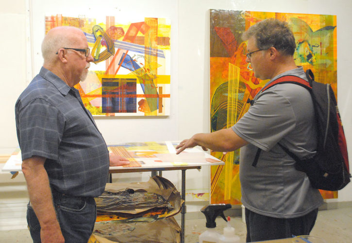 Artist Frank Owen discusses his work with neighbor Tom Fine in July 2015 at Own's home in Keene Valley, part of the Studio Tour. (Enterprise photo — Matthew Turner)