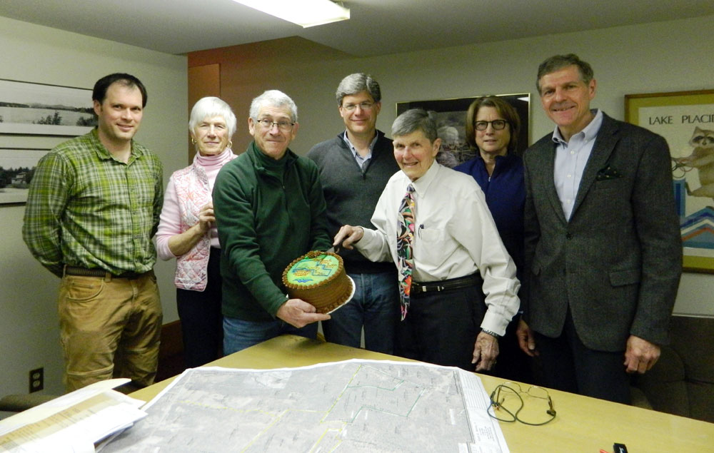 """Board members and staff of the Lake Placid Land Conservancy and Barkeater Trails Alliance — from left, Matt McNamara, Georgia Jones, John Rosenthal, Jeffrey Graff, Scott Avery, Liz Clarke and Gregory Fetters — gather to celebrate closing a 100-acre land purchase that will be part of a new """"community forest preserve"""" in Wilmington. (Photo provided by the Lake Placid Land Conservancy)"""