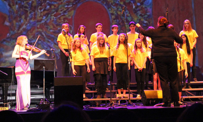 A choir from Saranac Lake Middle School performs with violinist Daisy Jopling, left, in April 2015 at the Lake Placid Center for the Arts.  (Photo provided — Naj Wikoff)