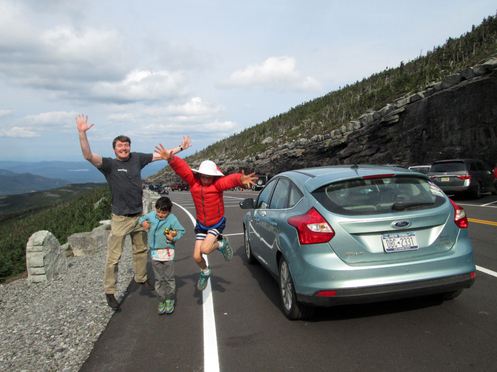 From left, Steve, Oliver and Galen Halasz jump for joy on the Whiteface Mountain Veterans Memorial Highway in Wilmington with their fully electric Ford Focus in summer 2015. (Photo provided by Sunita Halasz)