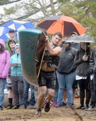 Paul Smith's senior Justin Tamez begins running in the rain after completing the paddle portion of the team portage competition Friday at the Spring Meet in Paul Smiths. Tamez paddled out and around a buoy in Lower St. Regis Lake, then carried the canoe about 100 yards to his teammate Nick Georgelas, who carried it back and completed the same paddling route. (Enterprise photo — Justin A. Levine)