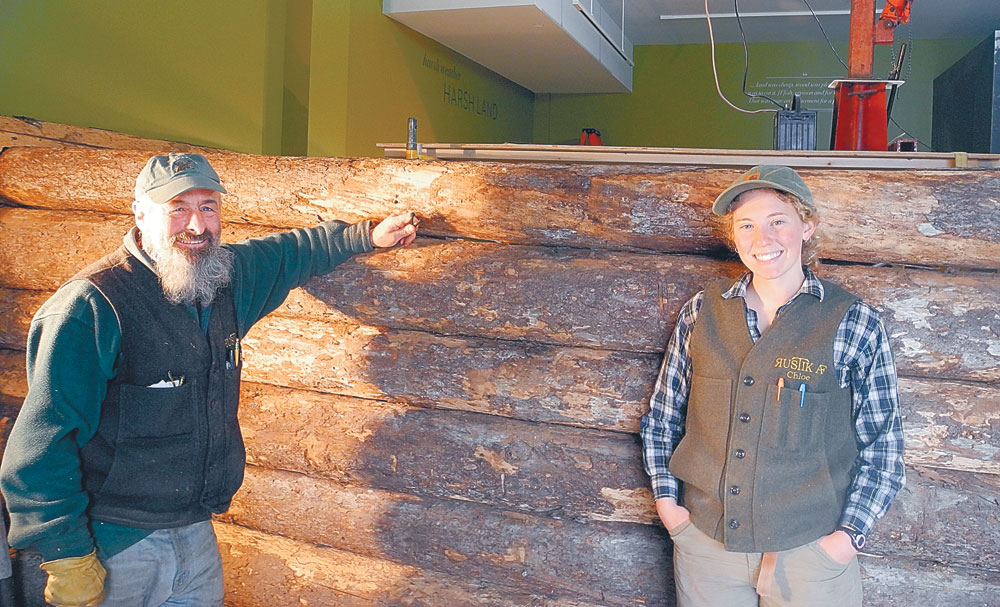 "Michael Frenette and Chloe Mattilio pose Thursday with their in-progress reassembly of ""Woodswoman"" author Anne LaBastille's log cabin inside the Adirondack Experience museum in Blue Mountain Lake. They previously disassembled the cabin from its original location at Twitchell Lake near Big Moose. (Enterprise photo — Ben Gocker)"