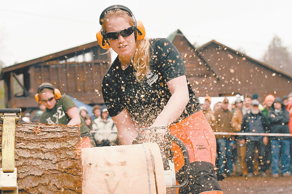 Emily DeYoung of the Paul Smith's College Bobcats competes in the stock saw event Saturday while earning a berth in the women's timbersports national championships that will be held in October. (Enterprise photo — Lou Reuter)