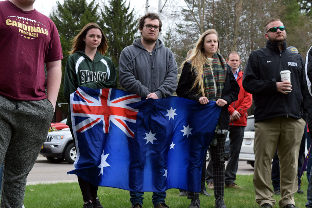 A group of North Country Community College students from Australia hold their country's flag during the village of Saranac Lake's Anzac Day ceremony on Tuesday.  (Enterprise photo — Chris Knight)