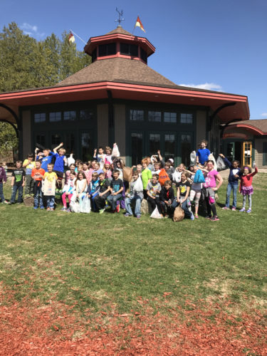 Petrova Elementary School third-grade students pose for a picture outside the Adirondack Carousel in Saranac Lake on Monday after they spent time cleaning up various parks around the village in recognition of of Earth Day. (Photo provided — Ali McCormick)