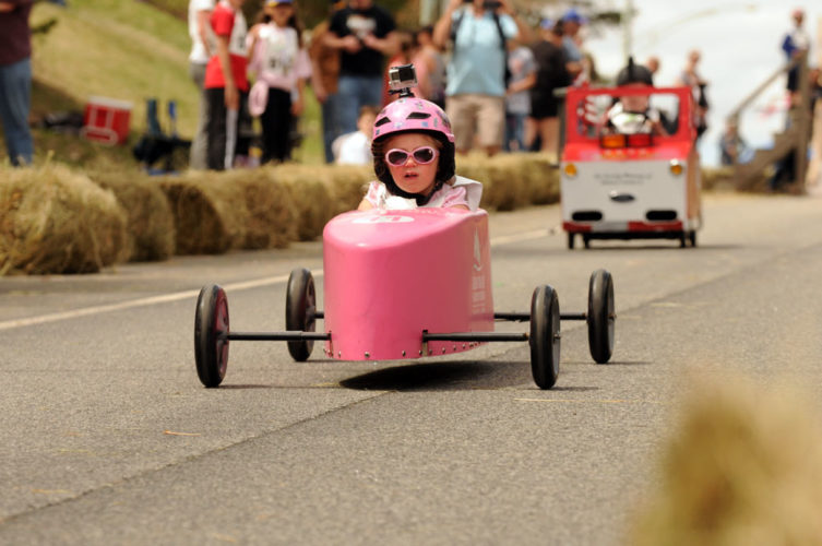 A girl drives a soap-box race car down the LaPan Highway hill in last year's Daffest Derby.  (Enterprise photo — Lou Reuter)