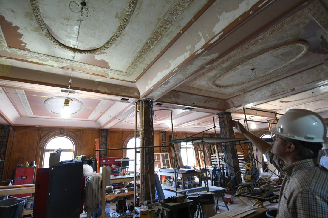 Hotel Saranac renovation project manager Tad Schrantz points to work being done on the ceiling of the ballroom during a tour of the site Thursday morning. The ballroom has also been serving as a woodshop during construction.  (Enterprise photo — Lou Reuter)