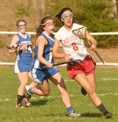 Lindsay Rath goes on the attack for Saranac Lake while rushing past Ogdensburg's Maria Pelasi during the opening half of Thursday's match. Rath paced the Red Storm with four goals. (Enterprise photo — Lou Reuter)