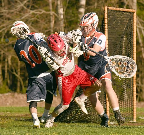 Saranac Lake's JB Chapin finds himself sandwiched by Potsdam defenders Sean O'Gorman (6) and Keenan O'Gorman during the second half of Friday's game. (Enterprise photo — Lou Reuter)