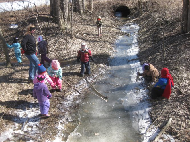 PHOTO BY VICKI JOHNSON Out & About Preschool students explore an iced-over creek during class at Garlo Heritage Nature Preserve near Bloomville.