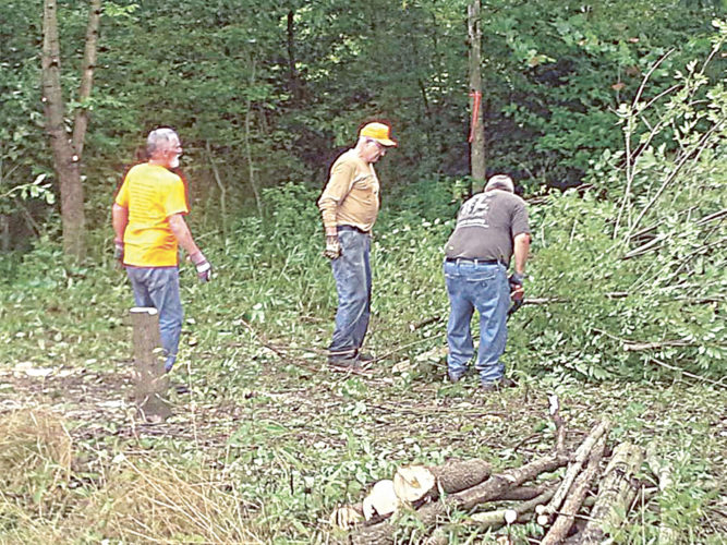 Bill Reinhart (with chain saw) and fellow volunteers Fred Smith (to his right) and Lenzy Marsillett cut up wood at the Kildow property.