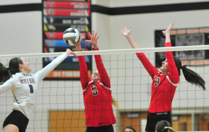 PHOTO BY PAT GAIETTO Mohawk's Chelsey Trusty (left) and Emily Connor jump to block Willard's Lydia Wiers during the Division IV district match in Attica Wednesday.