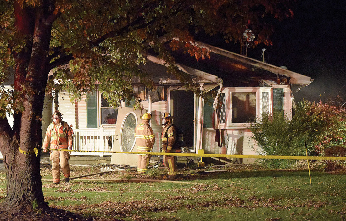 PHOTO BY JILL GOSCHE Firefighters work at the scene of a house fire at 2207 S. SR 587 Wednesday night.
