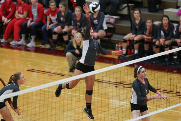 PHOTO BY STEVE WILLIAMS Buckeye Central's Jenna Karl (5) goes high for an attack, as teammates Addie Ackerman (4) and Sarah Heydinger (6) set up to defend return play at Willard Thursday.