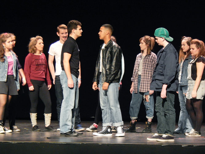 """PHOTO BY NICOLE WALBY Noah Stephen, as Jim Stark (center left), and Tyrek Hyde, as Buzz Gunderson (center right), face off Tuesday night during a dress rehearsal of the Ritz Teen Thespian Guild's production of """"Rebel Without A Cause."""""""