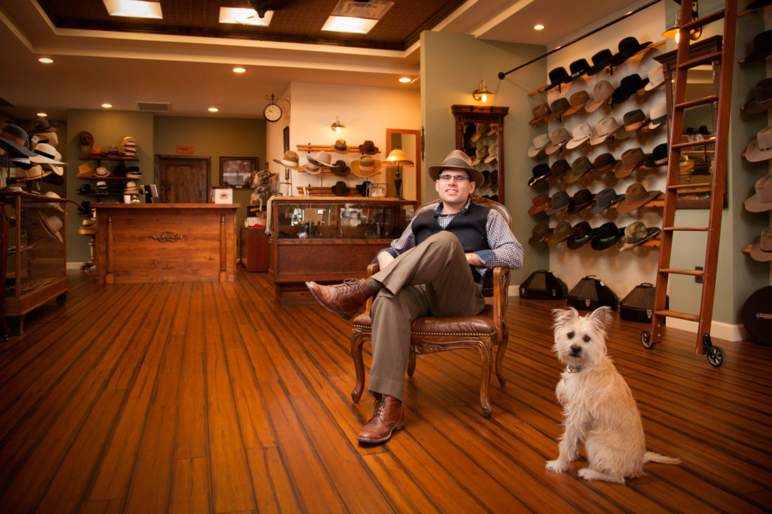 PHOTO SUBMITTED Eric Watson poses in his store with shop dog, Derby.