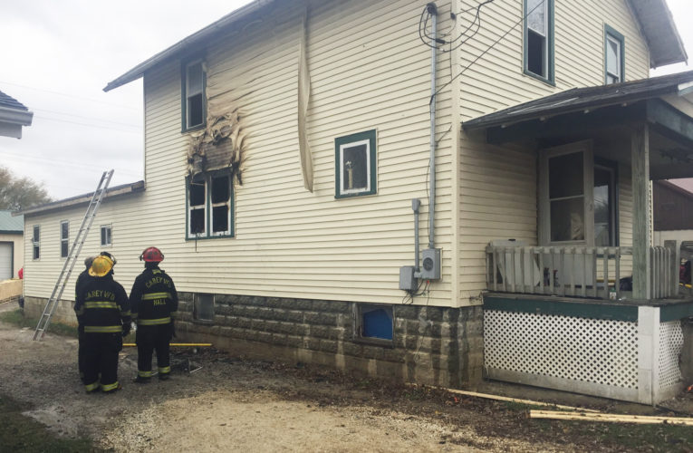 PHOTO BY SETH WEBER Firefighters examine damage to the Carey residence after it caught fire Thursday afternoon.