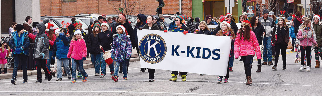 PHOTO BY JILL GOSCHE Members of Tiffin City Schools' K-Kids group walk down Washington Street during Kiwanis Club of Tiffin's Christmas parade Saturday morning. To view more photos from this event, visit cu.advertiser-tribune.com.