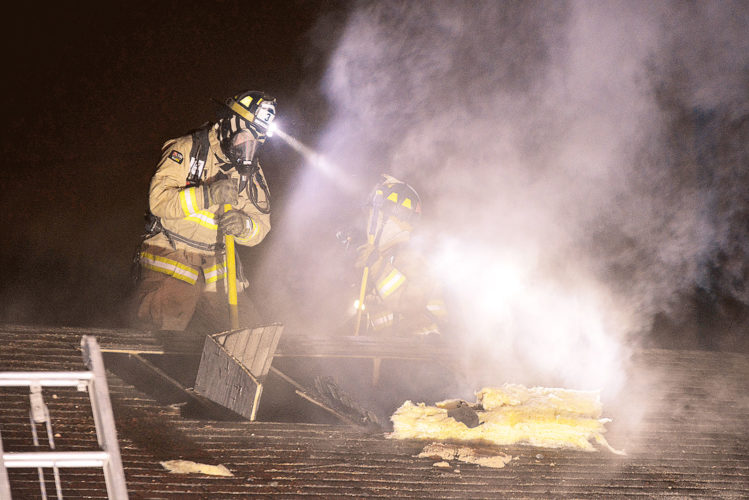 PHOTO BY JILL GOSCHE Tiffin Fire Rescue Division personnel work on the roof of 45 Elmwood St. early Monday morning.
