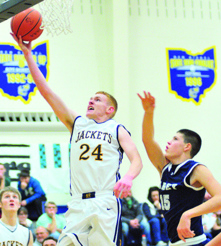 PHOTO BY PAT GAIETTO New Riegel's Shane Halcomb shoots past Carey's Hayden Stone Friday in New Riegel.