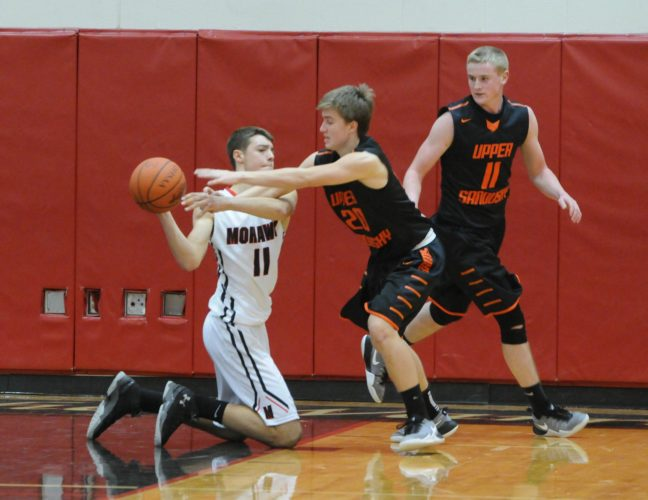 PHOTO BY JONATHON BIRD Mohawk's Damon Steinhauser looks to pass from his knees as he is pressured by Upper Sandusky's Evan Young and Eli Kinley Friday.