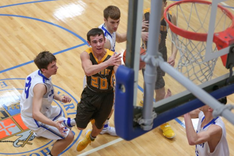 PHOTO BY STEVE WILLIAMS Old Fort's Jacob Webb sets his eyes on the basket after he splits Calvert defenders on his way down the lane for the score Saturday in Tiffin.