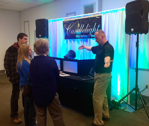 PHOTO BY SETH WEBER Larry DeVaughn (right), owner of Candlelight Disc Jockey Service, talks to attendees about his service during Camden Falls Wedding Showcase Sunday afternoon.