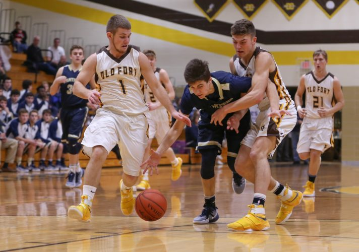 PHOTO BYSTEVEWILLIAMS Old Fort's Luke Wagner (left) and Eric Bell (right) fight for a loss ball against St. Mary's James Fischer (center), as the Stockaders' Jacob Hammond (21) trails the play Friday.