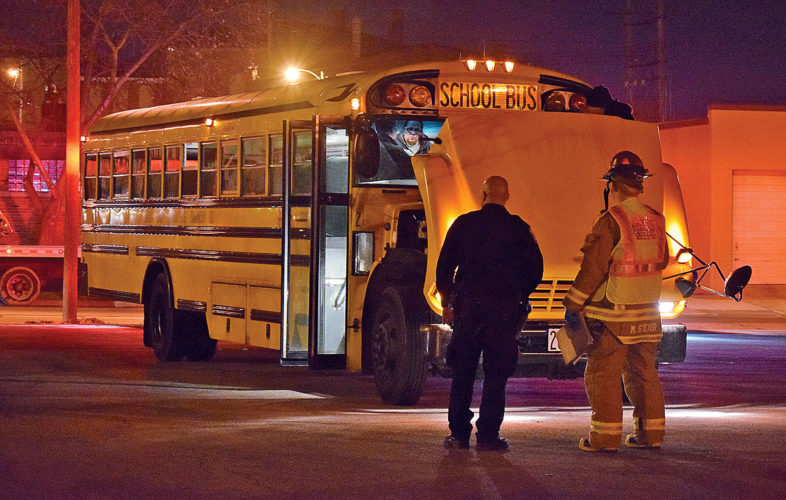 PHOTO BY JILL GOSCHE Officer Eric England (left) of Tiffin Police department and Capt. Mike Steyer of Tiffin Fire Rescue Division stand near a bus involved in a crash Thursday evening.
