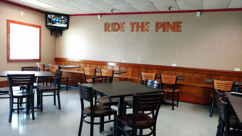 "PHOTO SUBMITTED The back wall of Benchwarmers Restaurant and Delivery, 105 Allen St., features wooden bleachers with the restaurant's slogan, ""Ride the Pine,"" on the wall above."