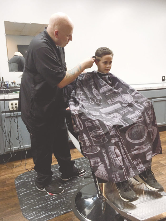 PHOTO BY ERIKA PLATT-HANDRU Camden Mooney, 10, gets a haircut from Nathan Smith, owner of N8's Barber Shop.
