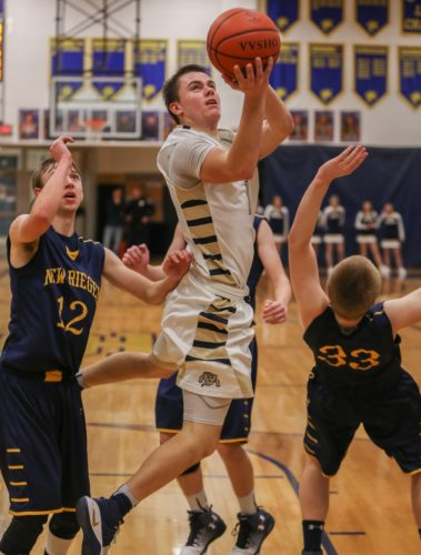 PHOTOBYSTEVEWILLIAMS Todd Simonds slices through New Riegel defenders Brian Hughes (12) and Austin Lescalett (33), to get a nice open look at the basket Saturday in Tiffin.