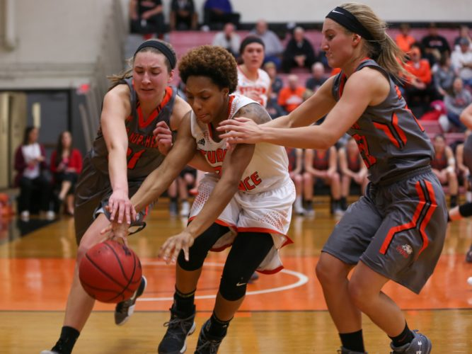 PHOTO BY STEVE WILLIAMS Heidelberg's Mariah Pearson (middle) chases down a loose ball against ONU's Jenna Dirksen (left) and Shannon Jack Wednesday in Tiffin.