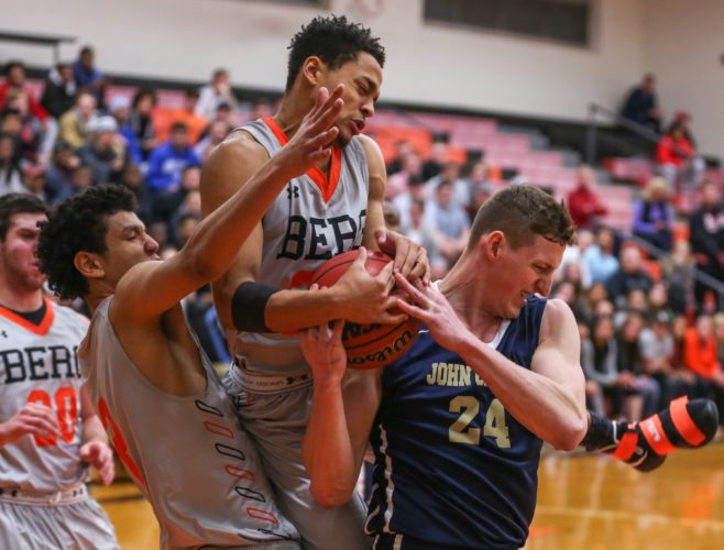 PHOTO BY STEVE WILLIAMS Heidelberg's Malik Quisenberry (middle) fights for a rebound over the shoulder of John Carroll's Simon Kucharewicz as Prince Benson and Andrew Grothouse (far left) stay close to the action Wednesday night in Tiffin.