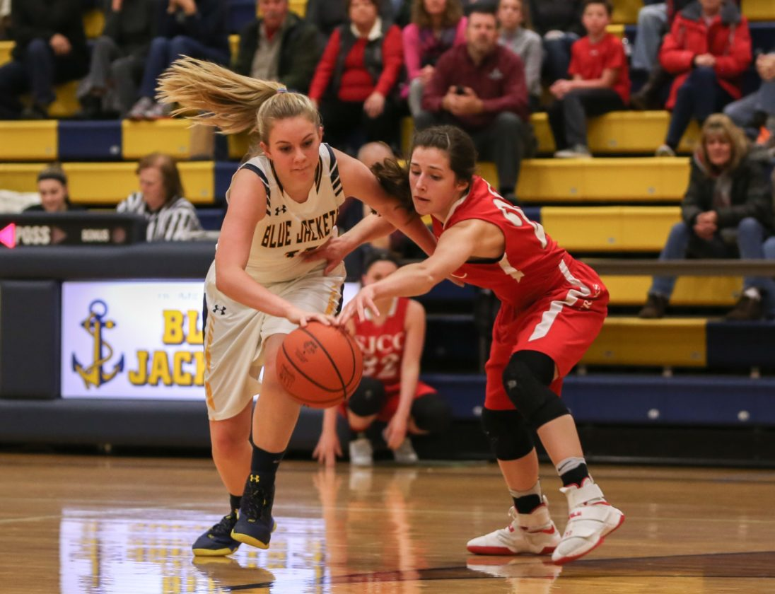 PHOTO BY STEVE WILLIAMS New Riegel's Haley Hoepf fights for control of a loose ball against St. Joe's Miranda Wammes Thursday.