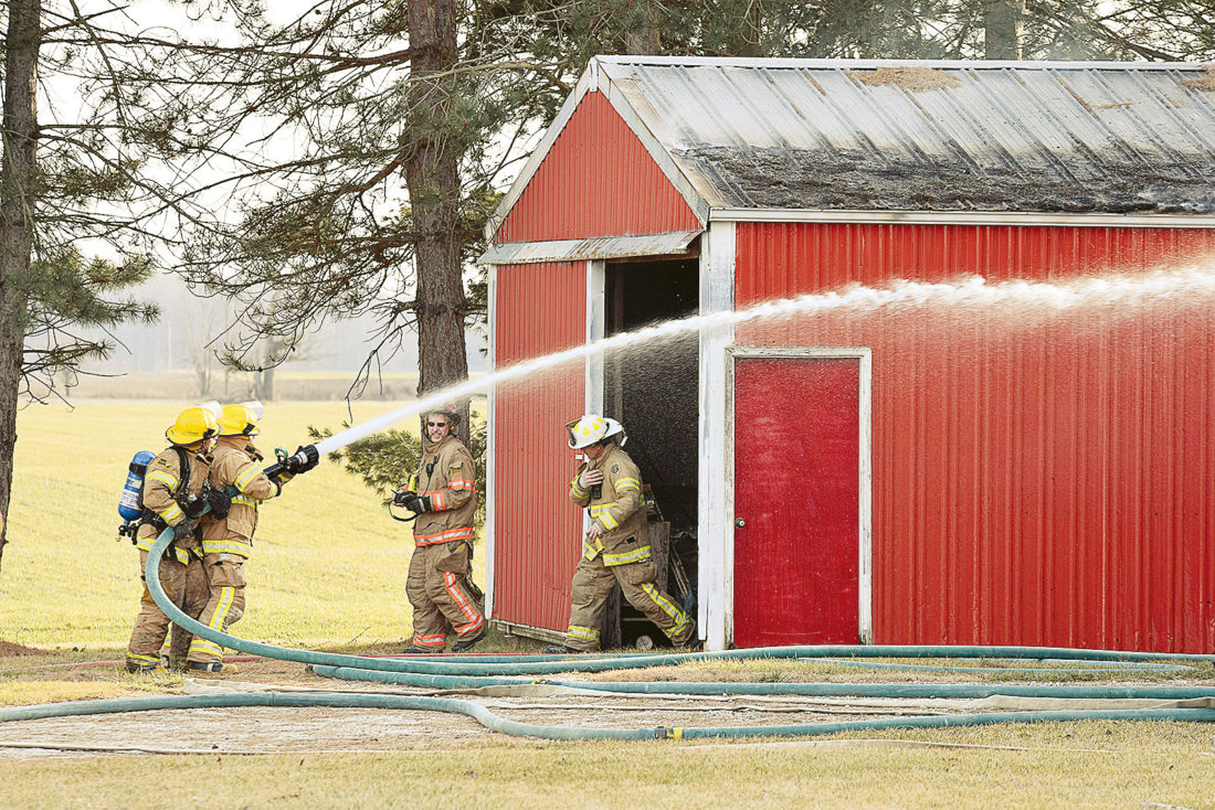 PHOTO BY JILL GOSCHE Firefighters work at the scene of a fire at 7540 W. CR 18 Monday.