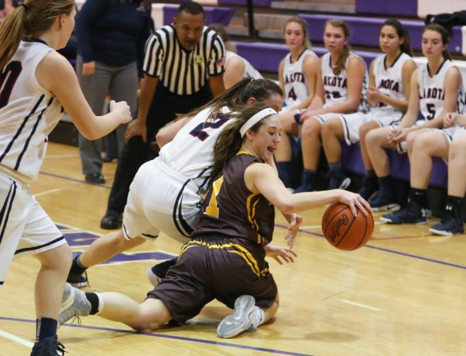 PHOTO BY STEVE WILLIAMS Old Fort's Allison Adelsperger maintains dribble control as she falls to the floor after contact with Lakota's Alexis Kirkpatrick Wednesday in a Division IV sectional semifinal at Fremont Ross.
