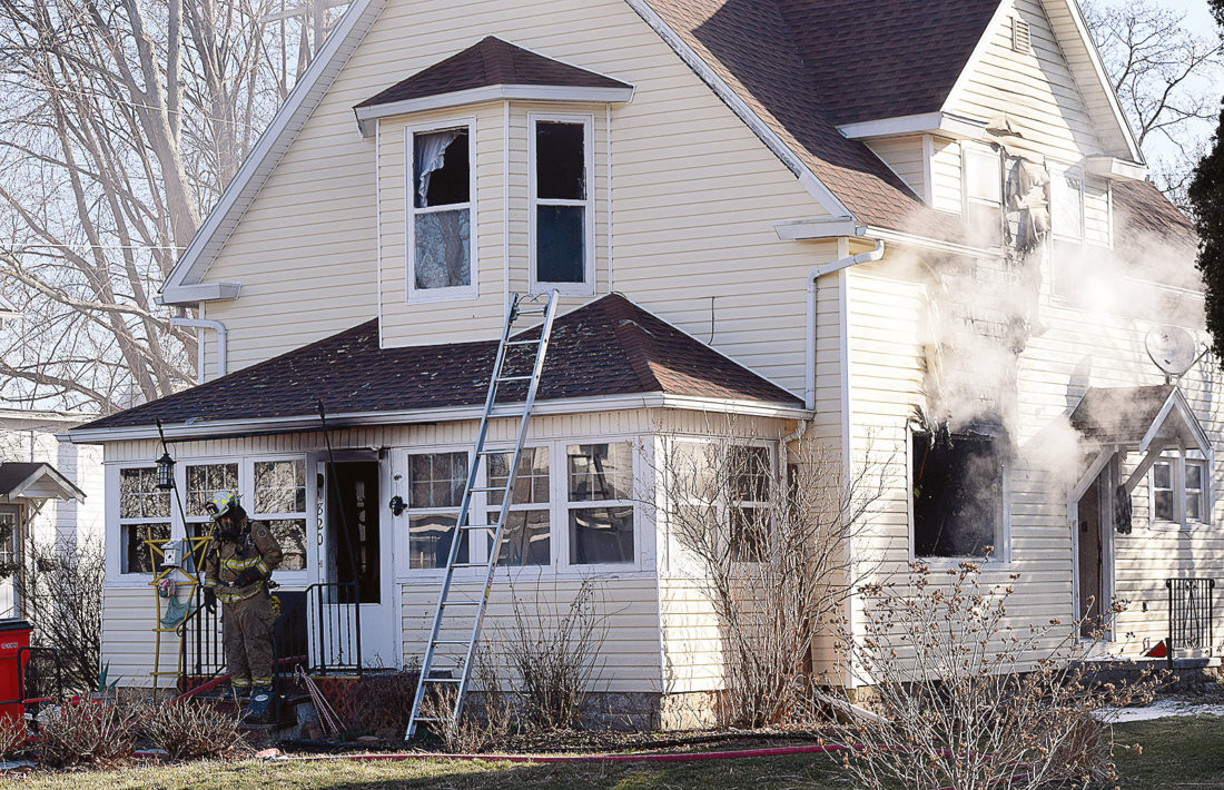 PHOTO BY JILL GOSCHE Smoke pours from the house at 820 S. Main St., Fostoria, Sunday morning.